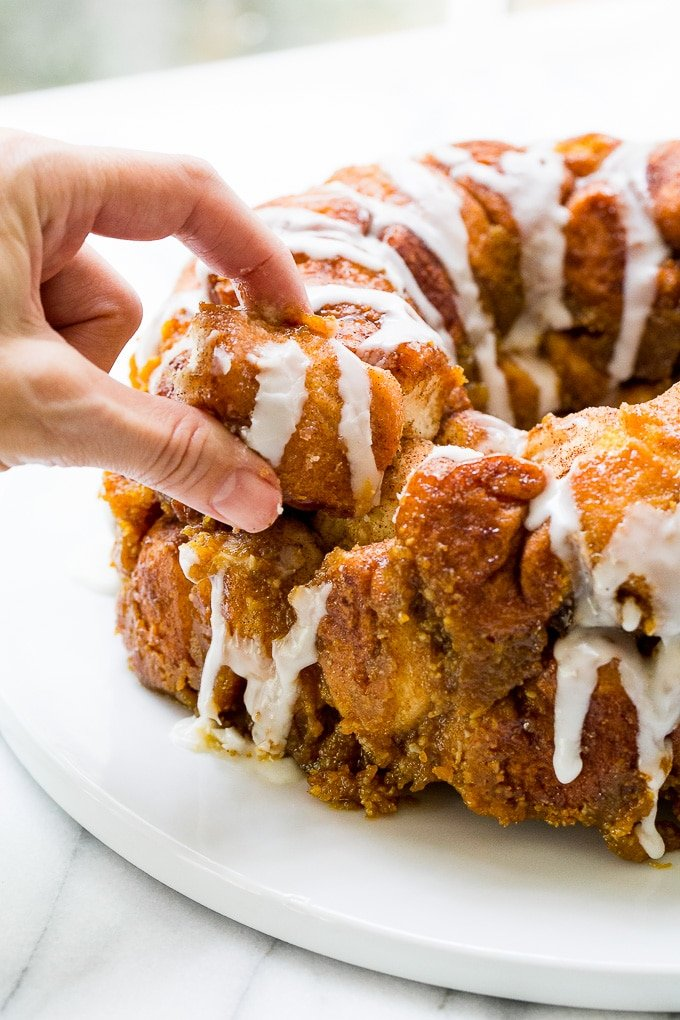 pulling off a piece of pumpkin monkey bread.