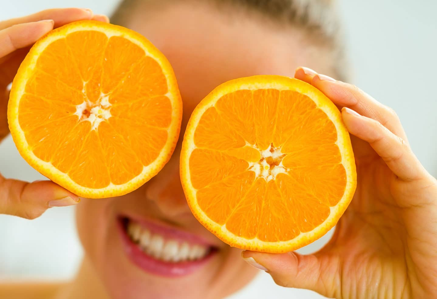happy young woman holding orange slices.
