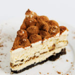 A slice of tiramisu cheesecake on a plate.