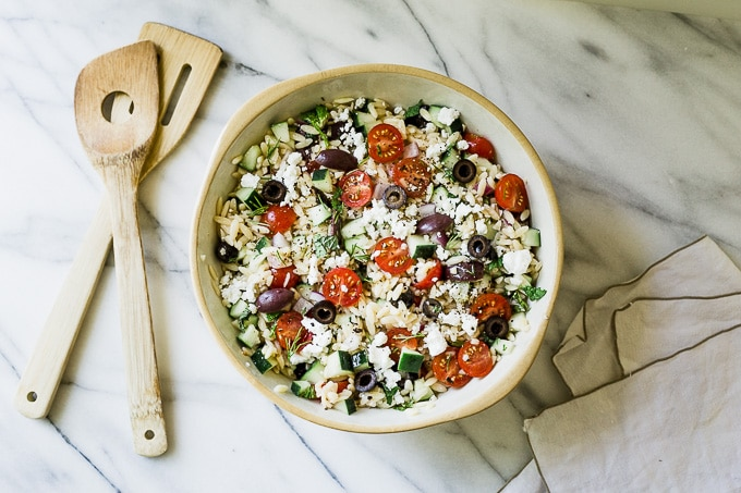 Greek Orzo Salad in a bowl with wooden spoons
