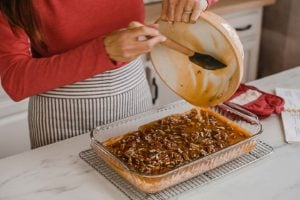 A woman pouring pecan pie filling over crust.