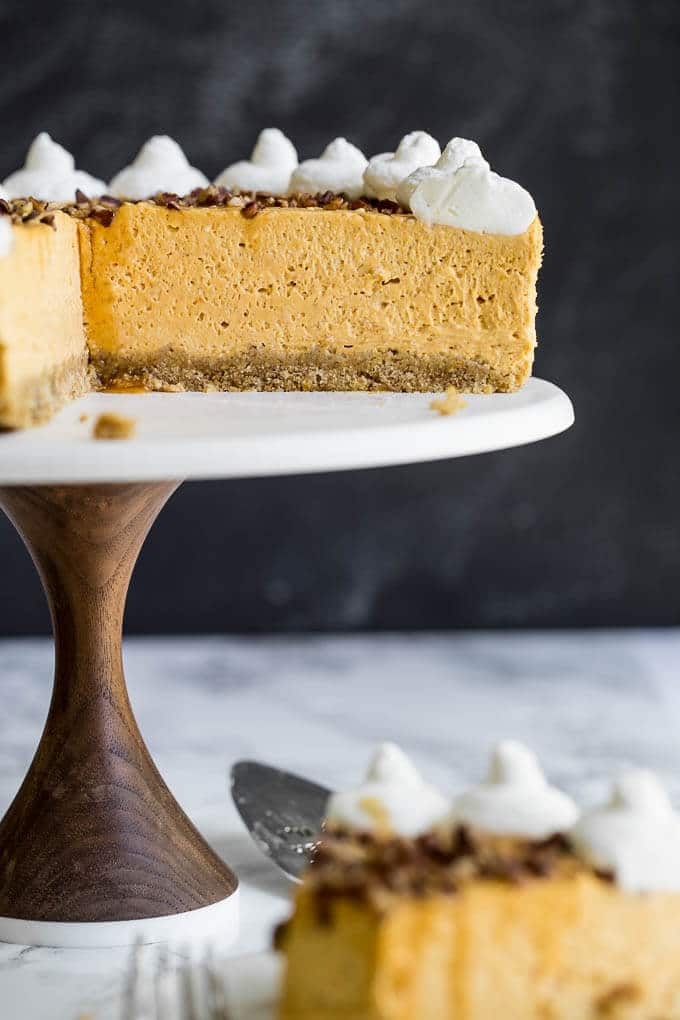 A pumpkin cheesecake on a cakestand with a slice taken out.