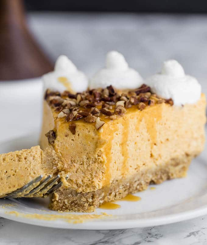 A slice of pumpkin cheesecake with a bite taken out.