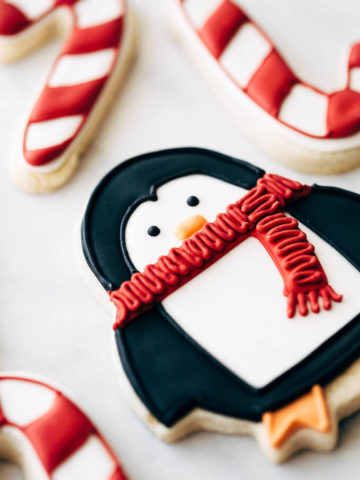 sugar cookies decorated like penguins and candy canes.