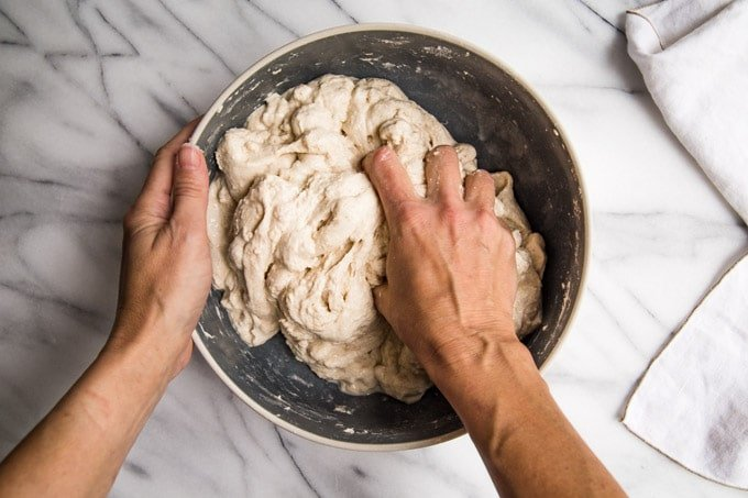 Hand mixing salt and extra water into dough.