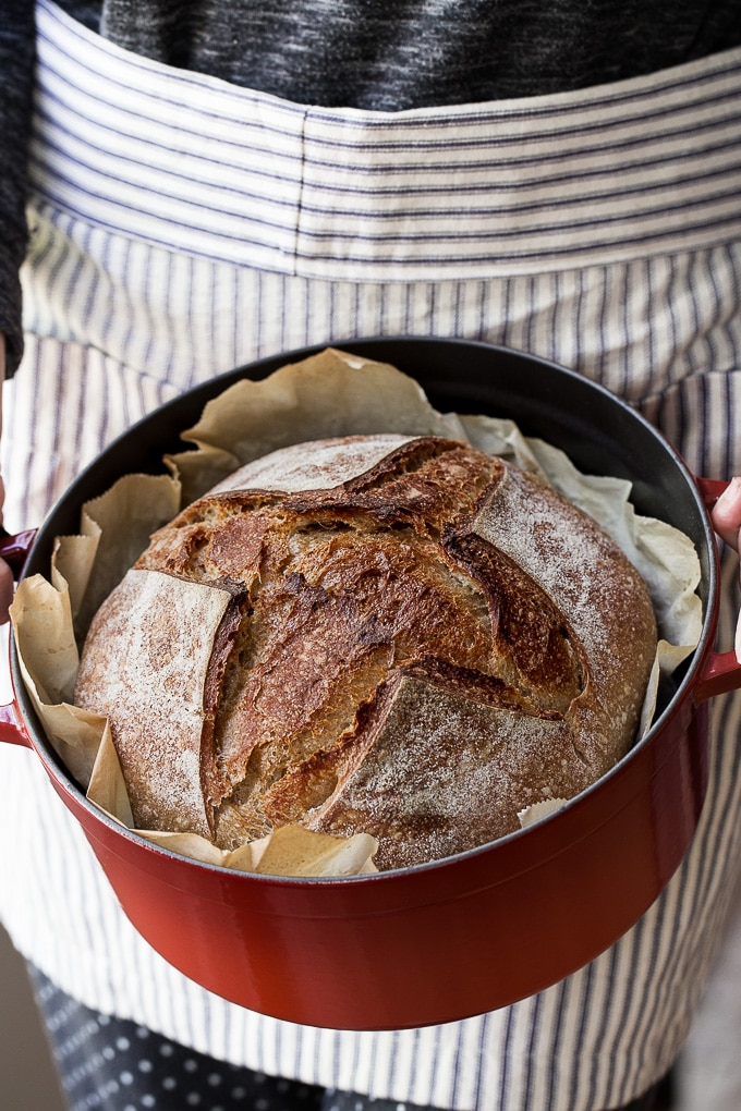 This easy Beginner's Sourdough Bread Recipe is made of three simple ingredients, flour, water and salt and there is no kneading required! The dough is left to slowly ferment and rise overnight, then baked in a Dutch oven to develop a crispy, golden brown crust. It is the perfect bread recipe for anyone that would like to try their hand at homemade sourdough bread! #sourdough #sourdoughbreadrecipe #artisanbread #easysourdoughrecipe #sourdoughstarter