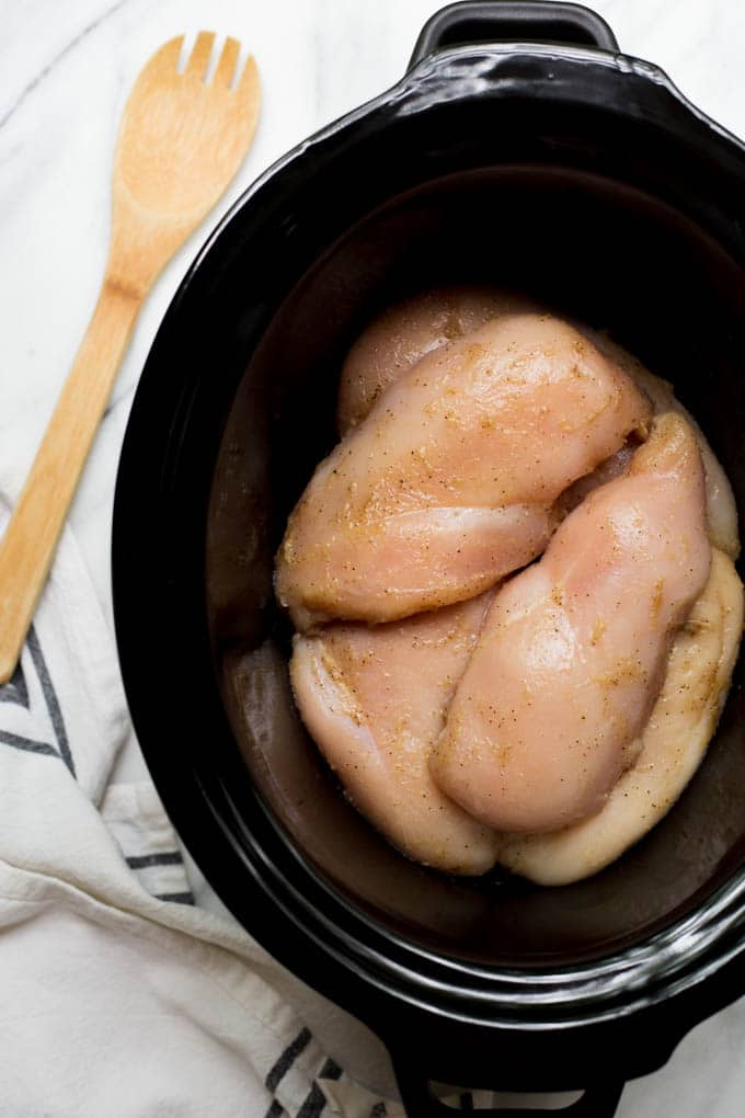 Seasoned, raw chicken breasts in a slow cooker.