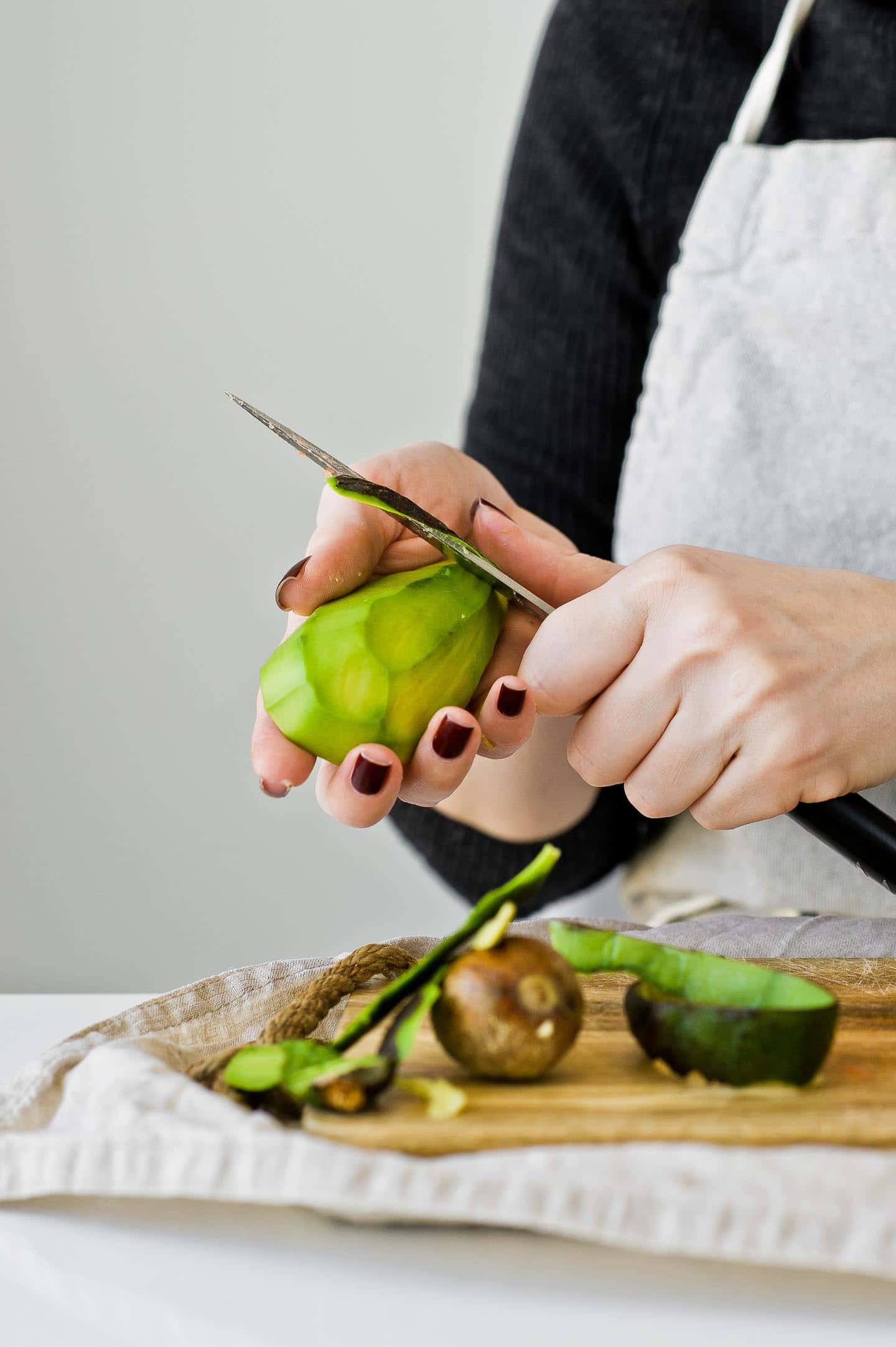 chef is peeling an avocado with a knife.