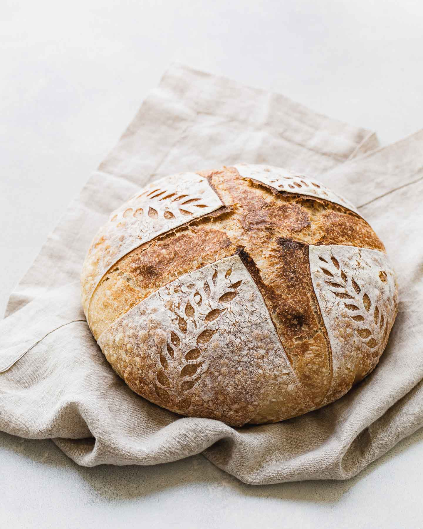 A beautiful loaf of sourdough bread on a linen napkin.