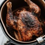 Air Fryer Whole Roasted Chicken is tender and juicy. Roast a whole chicken in less than an hour! #airfryerrecipe #roastedchicken #chickenrecipe #roastedchicken