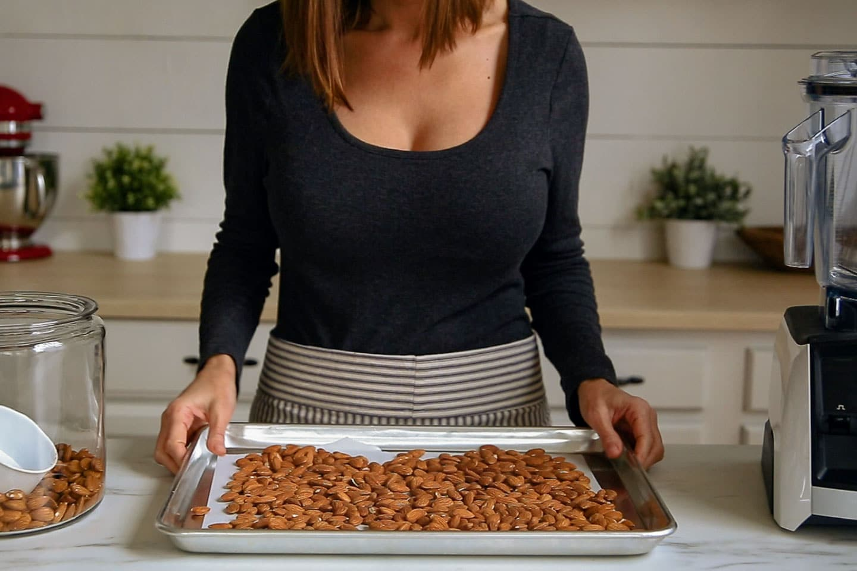 A woman holding a baking sheet of almonds.