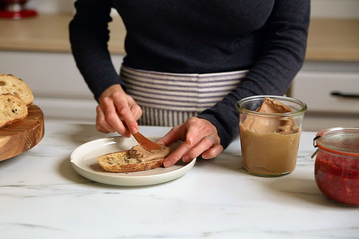 A woman spreading almond butter on a piece of toast.