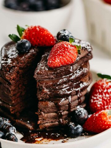 Gluten-Free Chocolate Pancakes are simple to make with wholesome ingredients. An allergy friendly pancake recipe with delicious hot chocolate sauce and berries. #glutefree #glutenfreepancakes #valentinesdayrecipe #chocolatepancakes #pancakes