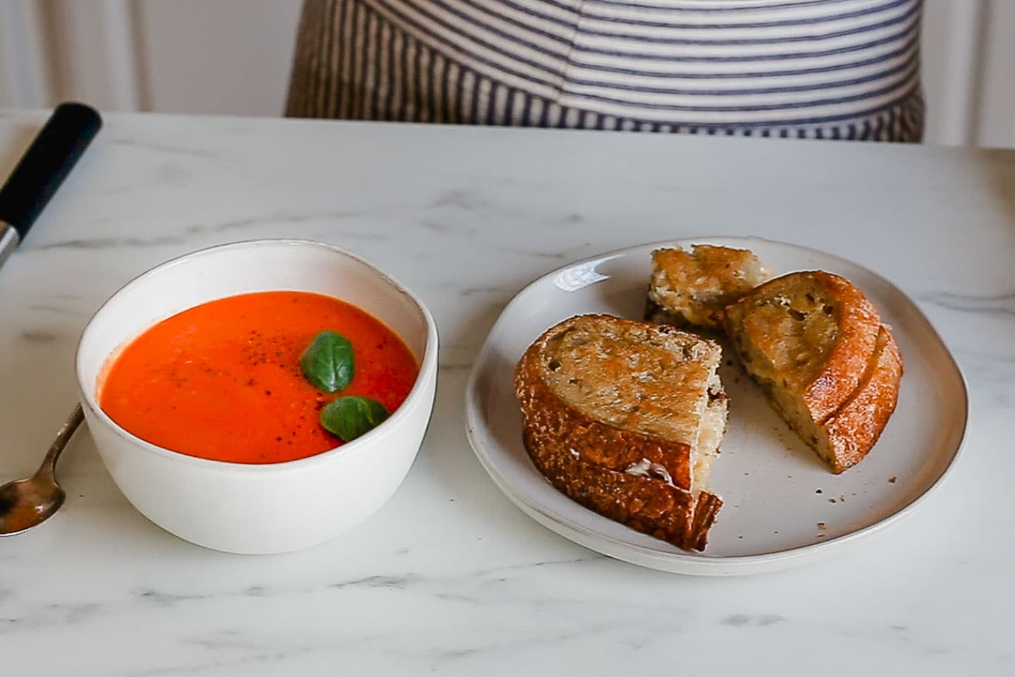 Bowl of soup and a grilled cheese sandwich on the table.