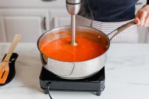 Blending homemade tomato soup with an immersion blender