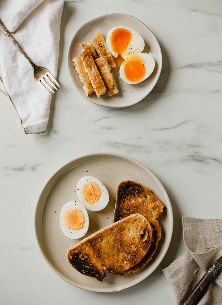 a plate of hard boiled eggs and soft boiled eggs with toast
