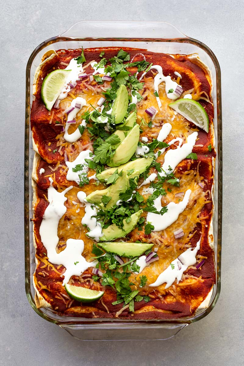 sweet potato enchiladas topped with cilantro avocado and sour cream