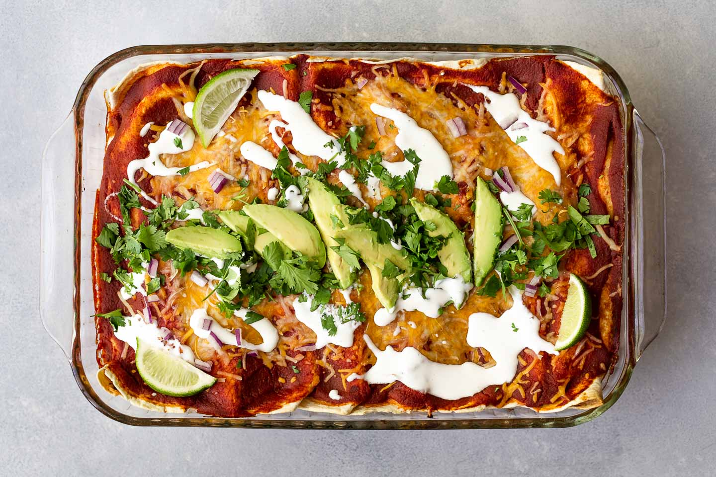 sweet potato enchiladas topped with avocado and cilantro.