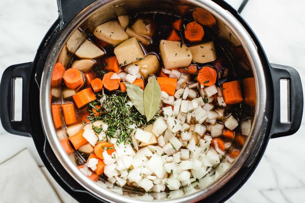 vegetables and herbs added to the instant pot beef stew.