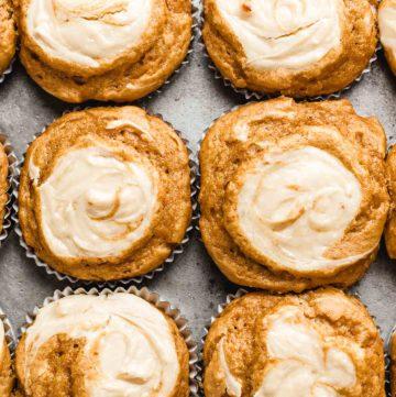 pumpkin cream cheese muffins in a baking tin.