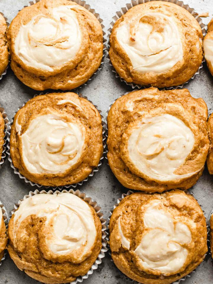 pumpkin cream cheese muffins in a baking tin.