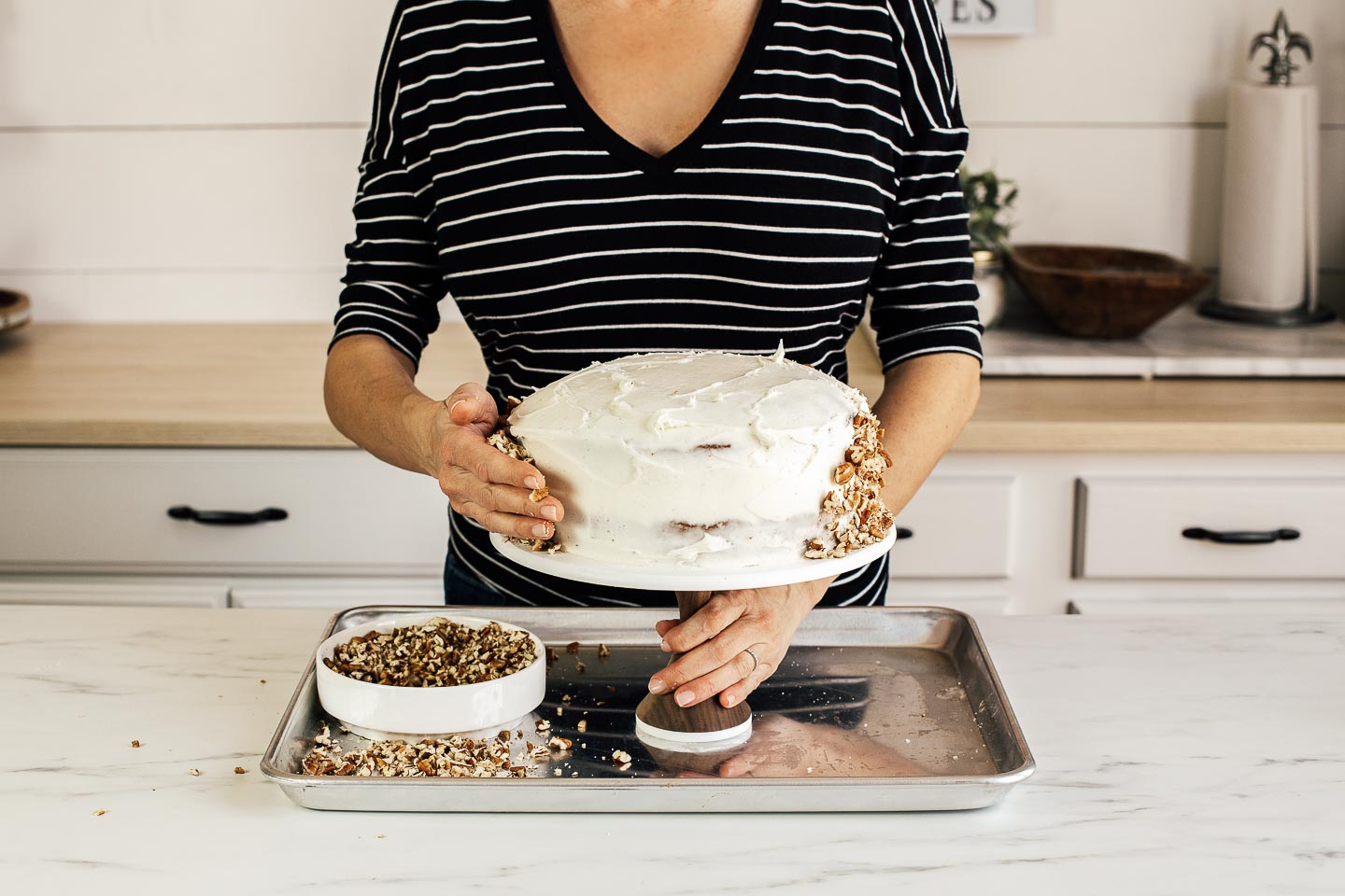 A woman decorating a cake with pecans.