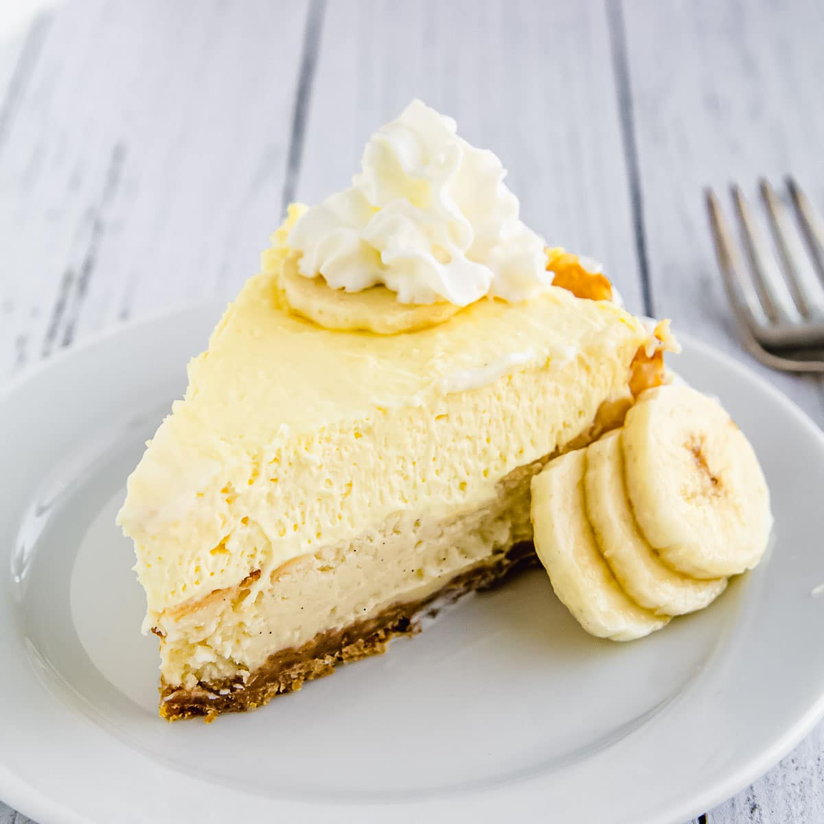 A slice of banana cream cheesecake on a plate.