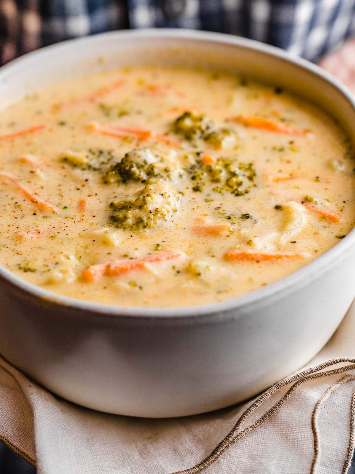 A woman holding a bowl of broccoli cheese soup.