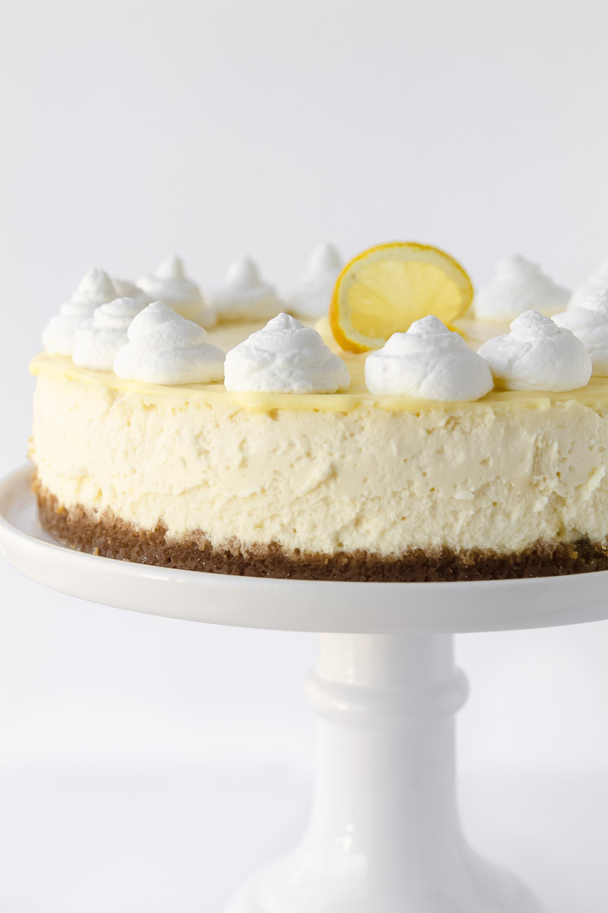 A lemon cheesecake topped with lemon curd and whipped cream.