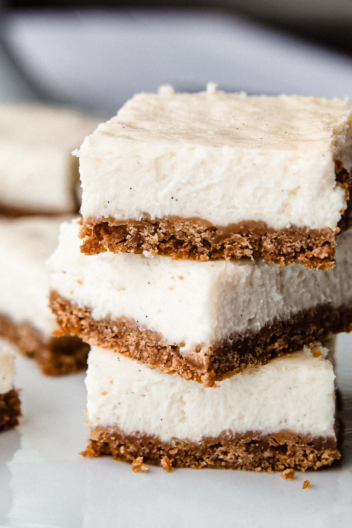 3 cheesecake bars stacked on a plate.
