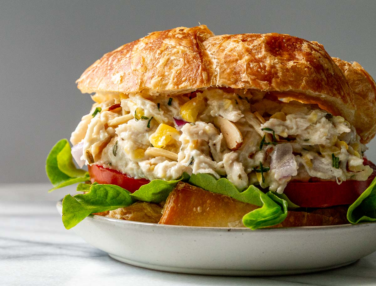 Tarragon chicken salad on a bun with lettuce and tomato.