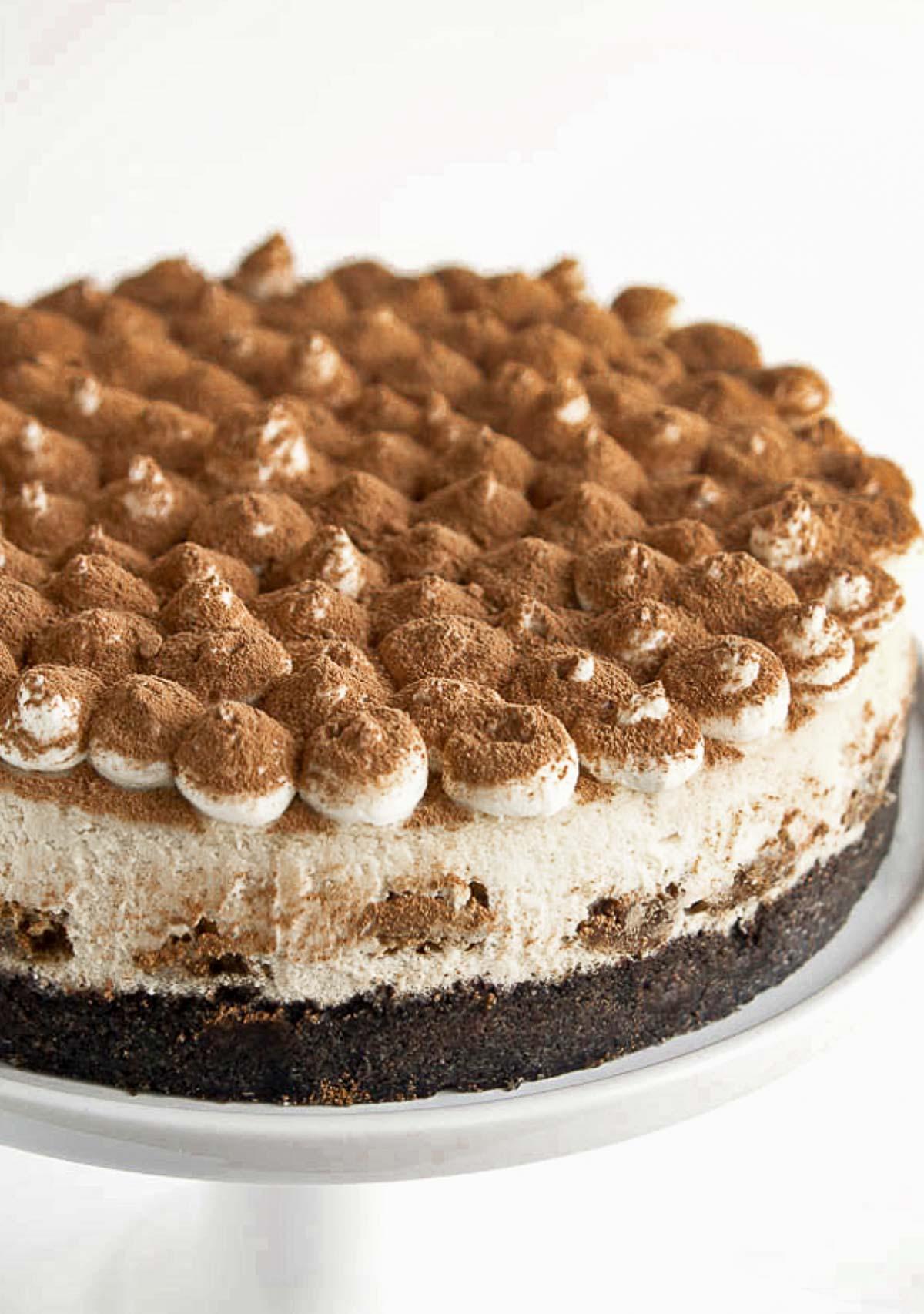 A tiramisu cheesecake on a cakestand.
