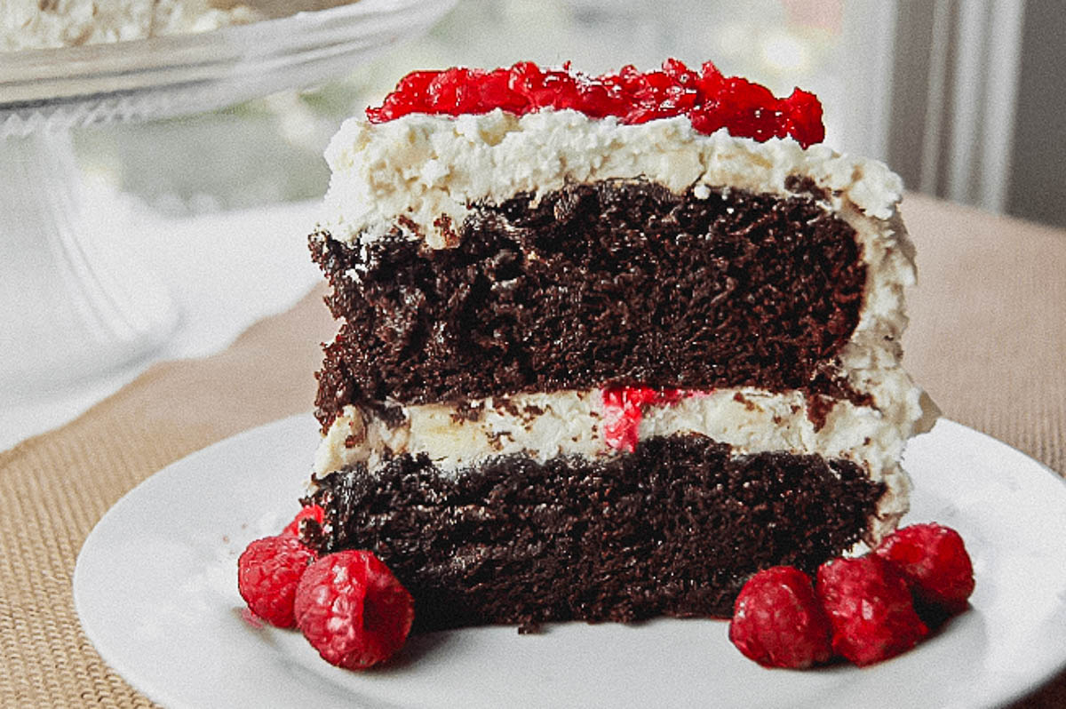 A slice of chocolate cake on a plate with raspberries.