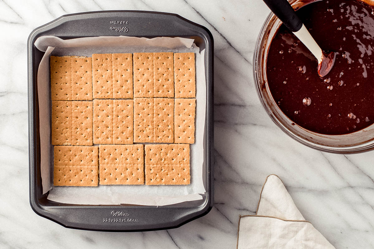 Graham crackers assembled in the bottom of a baking pan.