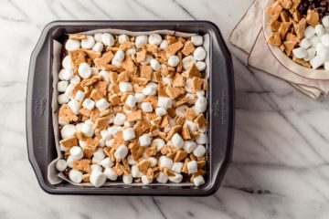 marshmallow and Graham crackers on brownies in a pan.