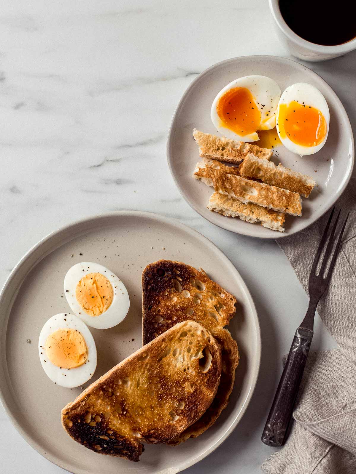 Hard and soft boiled eggs with toast on two plates.