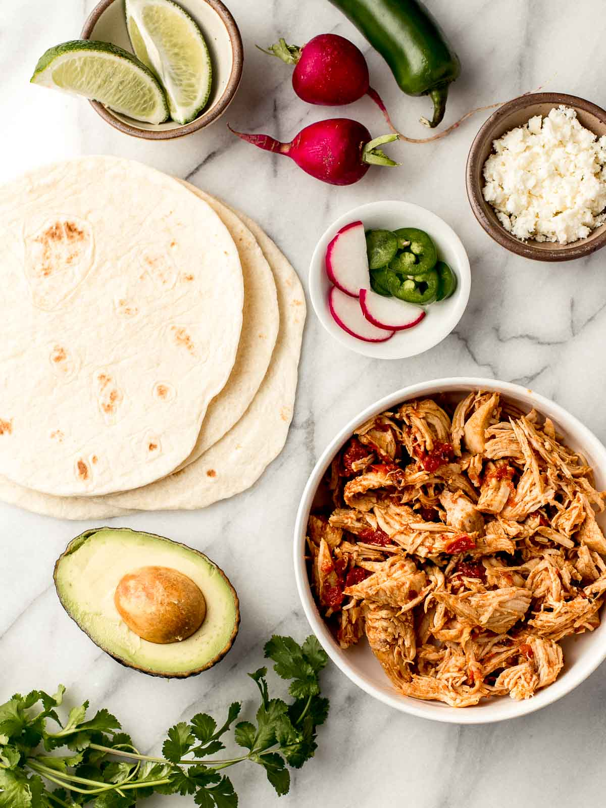 Mexican Shredded Chicken tacos ingredients on a table.
