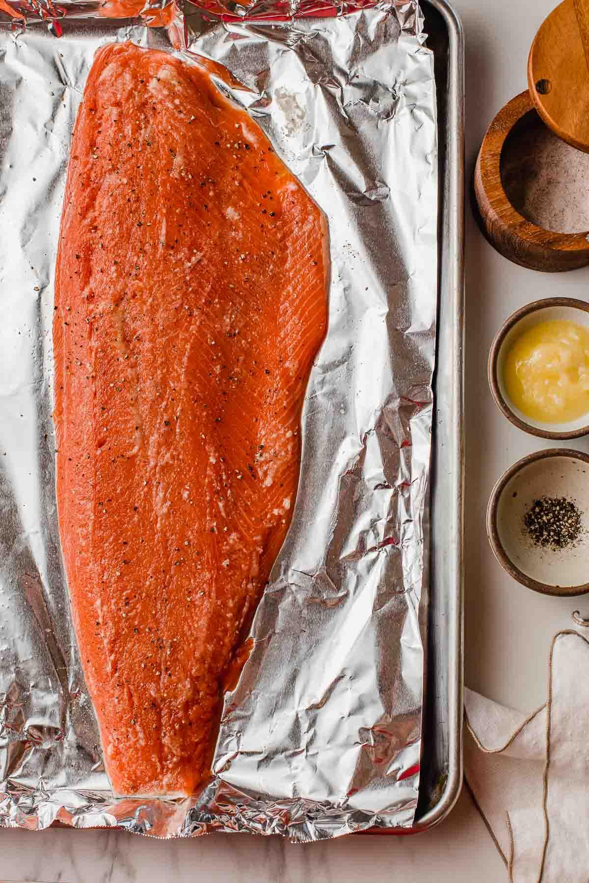A salmon fillet on a baking sheet.