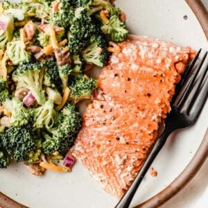 A piece of baked salmon on a plate with broccoli salad.