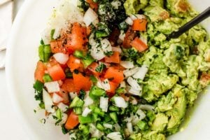 A mixing bowl with avocado ingredients.