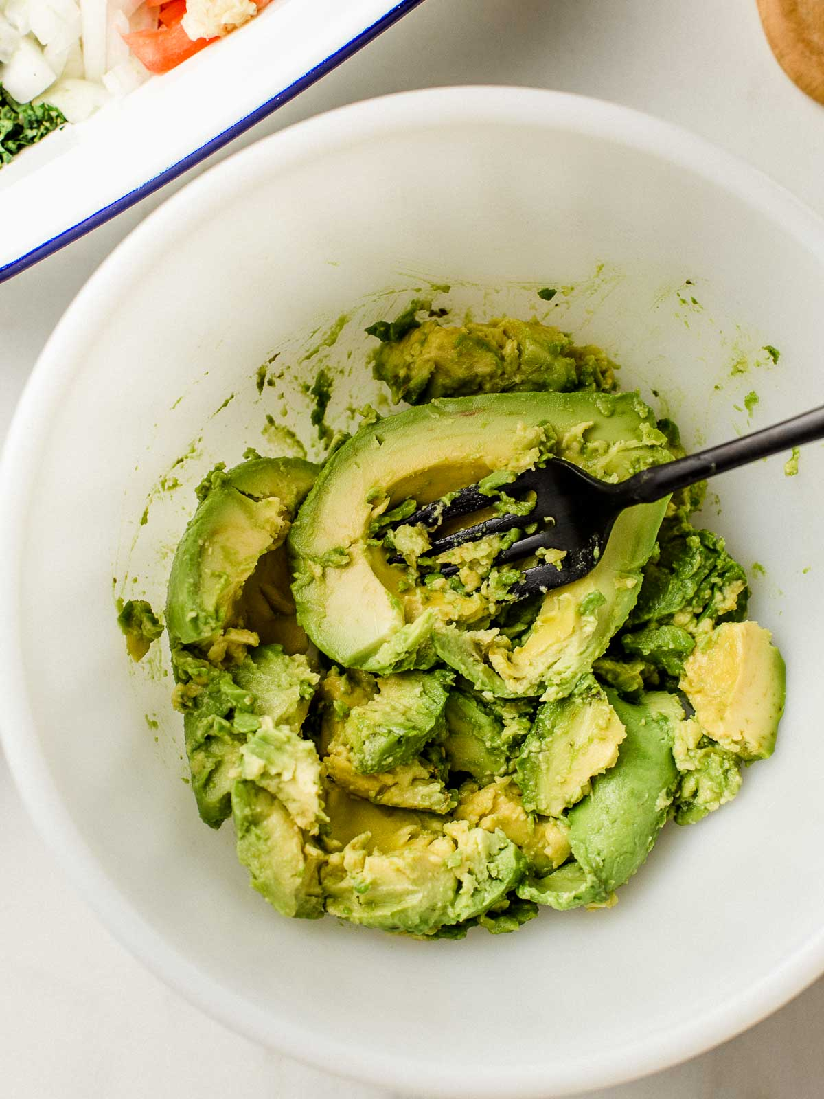 Mashed avocado in a bowl with a fork.