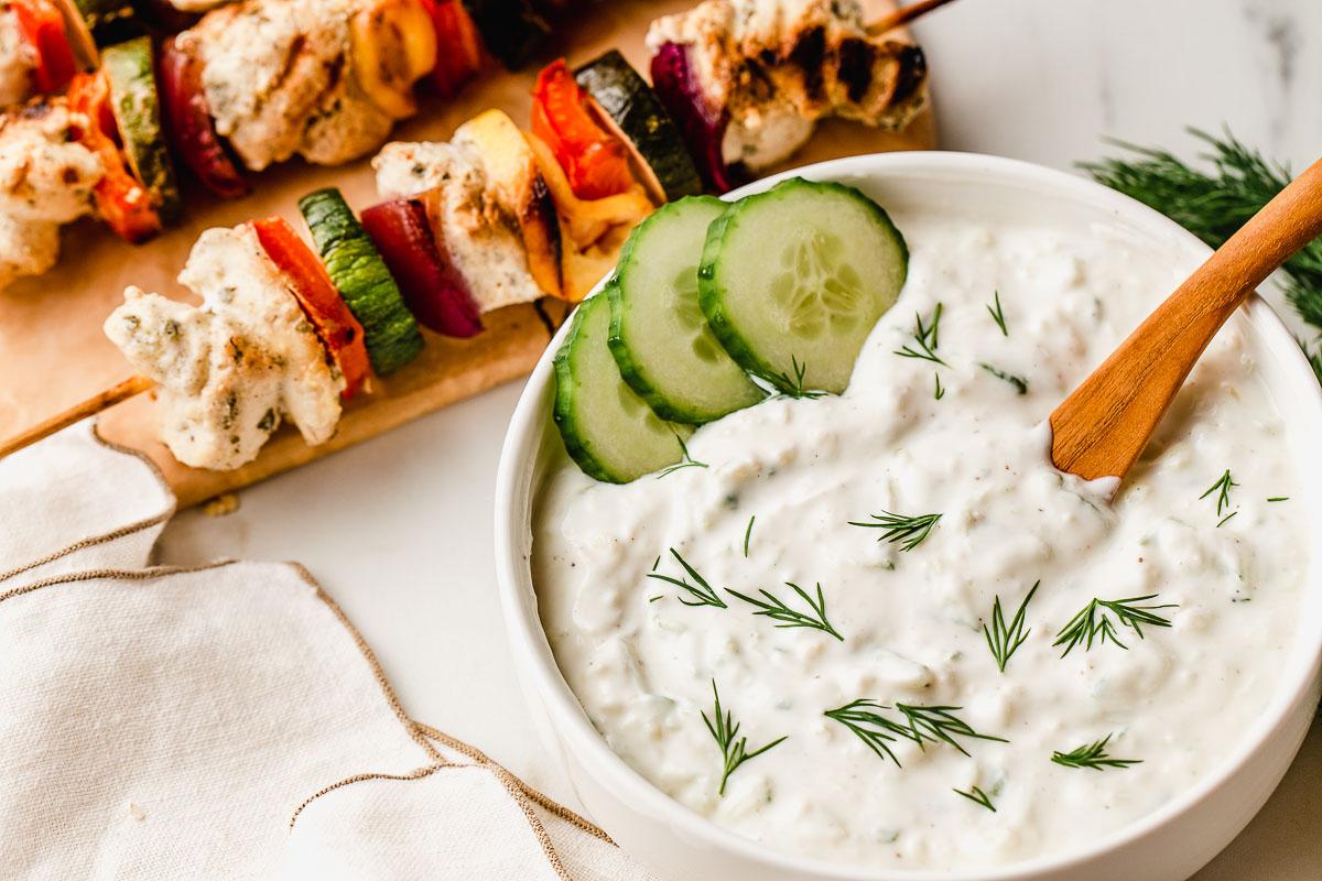 Tzatziki sauce in a bowl with chicken kabobs.